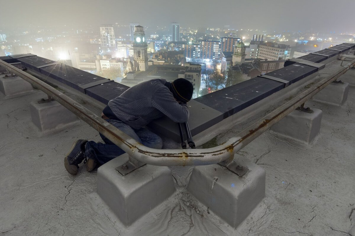 me laying on top of my tripod taking a long exposure on top of zuric house